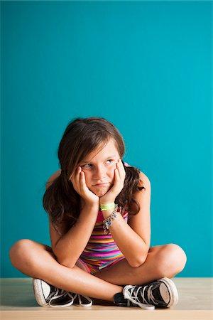 preteen girl pigtails - Portrait of girl sitting on floor looking upset, Germany Stock Photo - Premium Royalty-Free, Code: 600-06899901