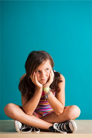 preteen girl pigtails - Portrait of girl sitting on floor looking upset, Germany Stock Photo - Premium Royalty-Free, Code: 600-06899901