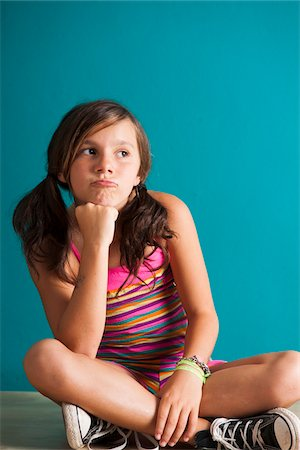preteen girl pigtails - Portrait of girl sitting on floor, pouting, Germany Stock Photo - Premium Royalty-Free, Code: 600-06899902