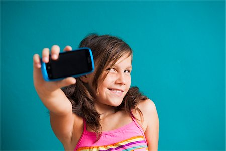 preteen girls faces photo - Close-up portrait of girl taking picture of herself with smartphone, Gremany Stock Photo - Premium Royalty-Free, Code: 600-06899903