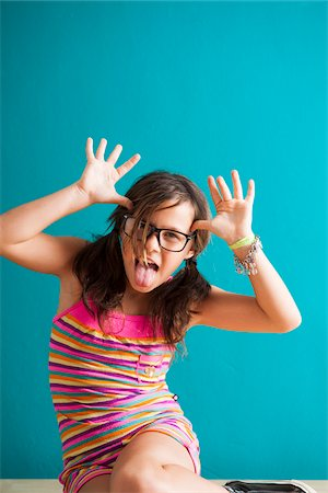 preteen girls faces photo - Portrait of girl sitting on floor making funny faces, Germany Stock Photo - Premium Royalty-Free, Code: 600-06899910