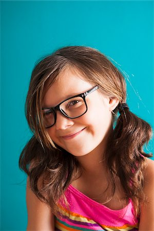 preteen girls faces photo - Portrait of girl wearing eyeglasses, smiling at camera, Germany Stock Photo - Premium Royalty-Free, Code: 600-06899913