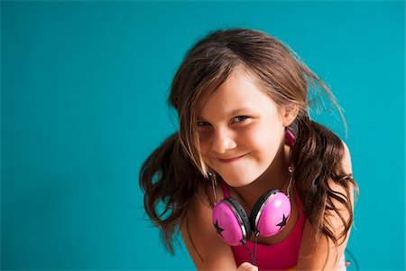 preteen girls faces photo - Portrait of girl wearing headphones around neck, looking at camera, making funny faces, Germany Stock Photo - Premium Royalty-Free, Code: 600-06899920