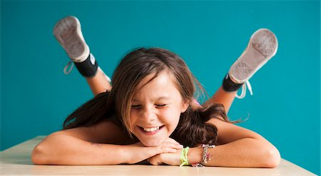 preteen girls faces photo - Girl lying on floor with eyes closed, making funny faces, Germany Stock Photo - Premium Royalty-Free, Code: 600-06899922