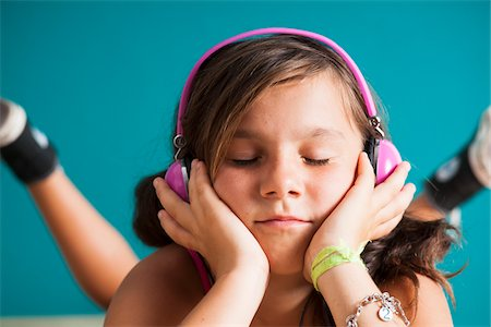 preteen girls faces photo - Close-up portrait of girl wearing headphones with eyes closed, Germany Stock Photo - Premium Royalty-Free, Code: 600-06899923