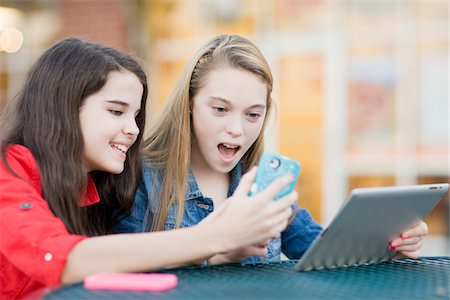 Pre-teen girls looking at cell phone and tablet computer, outdoors Stock Photo - Premium Royalty-Free, Code: 600-06892509