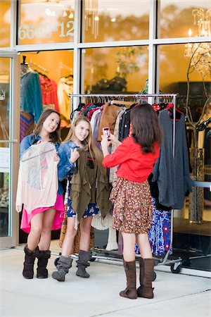 Pre-teen girls shopping for clothes and taking picture with smartphone Stock Photo - Premium Royalty-Free, Code: 600-06892510