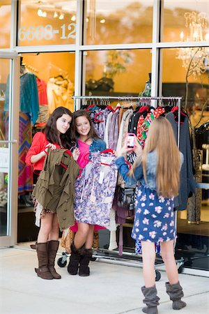 Pre-teen girls shopping for clothes and taking picture with smartphone Stock Photo - Premium Royalty-Free, Code: 600-06892511