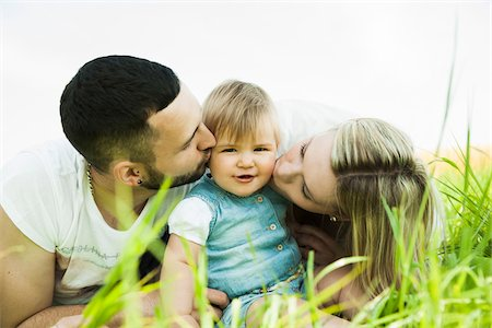 Portrait of Mother and Father Kissing Baby Daughter's Cheeks, Mannheim, Baden-Wurttemberg, Germany Stock Photo - Premium Royalty-Free, Code: 600-06892765