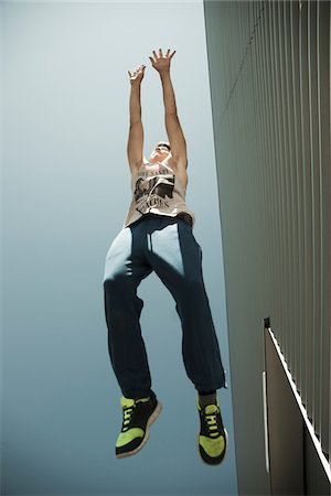 Low angle view of teenager jumping in midair, freerunning, Germany Stock Photo - Premium Royalty-Free, Code: 600-06900008