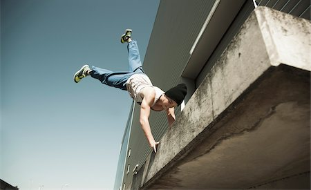 Low angle view of teenaged boy doing handstand on balcony, freerunning, Germany Stock Photo - Premium Royalty-Free, Code: 600-06900009