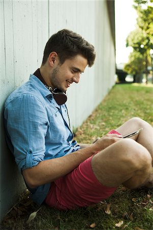 Young man sitting next to wall of building outdoors, with headphones around neck and looking at cell phone, Germany Stock Photo - Premium Royalty-Free, Code: 600-06900002