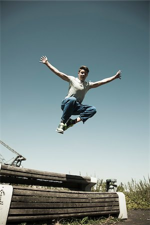 Low angel view of teenaged boy jumping over barrier, freerunning, Germany Stock Photo - Premium Royalty-Free, Code: 600-06900014