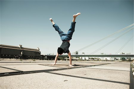 Teenaged boy doing handstand on cement road, freerunning, Germany Stock Photo - Premium Royalty-Free, Code: 600-06900021