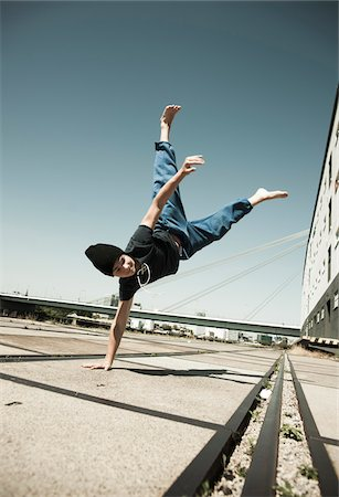 Teenaged boy doing handstand on cement road, freerunning, Germany Stock Photo - Premium Royalty-Free, Code: 600-06900022
