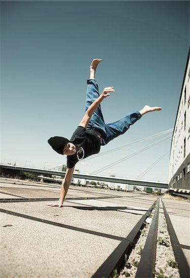 Teenaged boy doing handstand on cement road, freerunning, Germany Stock Photo - Premium Royalty-Free, Artist: Uwe Umstätter, Image code: 600-06900022