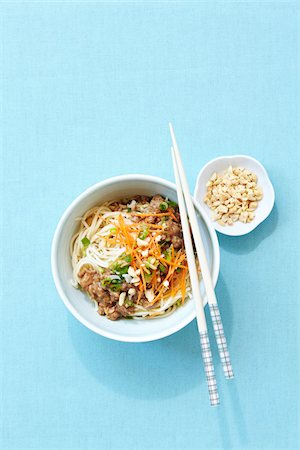 Overhead View of Noodles with Pork, Peanuts, and Shredded Carrot in Bowl with Chopsticks Stock Photo - Premium Royalty-Free, Code: 600-06934979