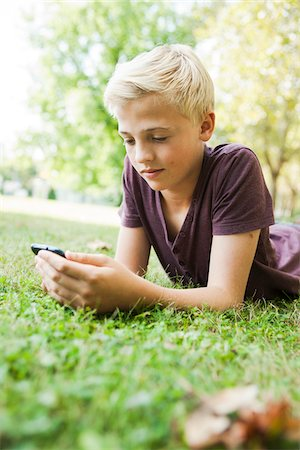Boy Lying on Grass using Cell Phone, Mannheim, Baden-Wurttemberg, Germany Stock Photo - Premium Royalty-Free, Code: 600-06939774