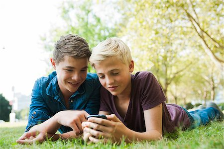 Boys using Cell Phone Outdoors, Mannheim, Baden-Wurttemberg, Germany Stock Photo - Premium Royalty-Free, Code: 600-06939775