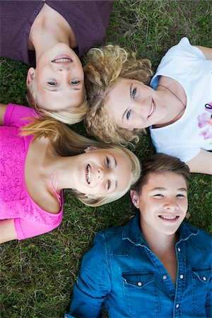 Overhead View of Teenagers Lying on Grass, Mannheim, Baden-Wurttemberg, Germany Stock Photo - Premium Royalty-Free, Code: 600-06939780