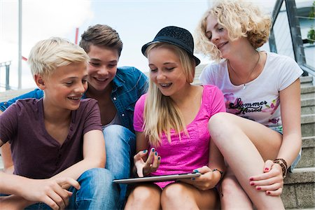 Group of teenagers sitting on stairs outdoors, looking at tablet computer, Germany Stock Photo - Premium Royalty-Free, Code: 600-06961018