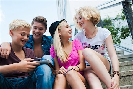 Group of teenagers sitting on stairs outdoors, looking at tablet computer, Germany Stock Photo - Premium Royalty-Free, Code: 600-06961019