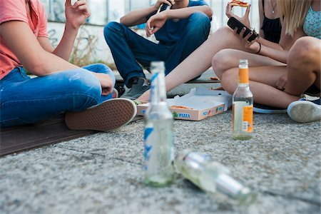 Surface level view of Group of teenagers sitting on ground outdoors, eating pizza and hanging out, Germany Stock Photo - Premium Royalty-Free, Code: 600-06961024