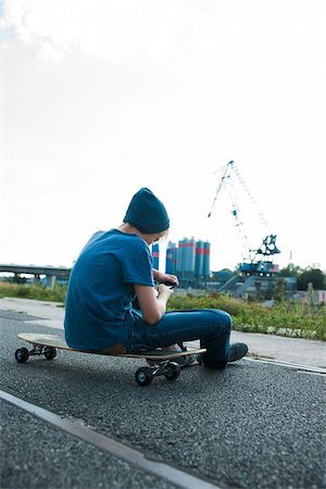device - Backview of boy sitting on skateboard outdoors in an industrial area and looking at cell phone, Germany Stock Photo - Premium Royalty-Free, Code: 600-06961025