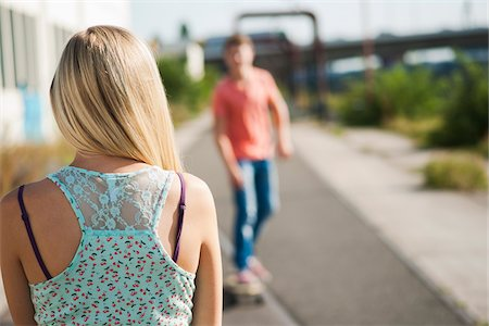 Backview of teenage girl in foreground and teenage boy on skateboard in background, Germany Stock Photo - Premium Royalty-Free, Code: 600-06961029
