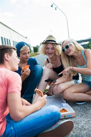 Group of Teenagers sitting on ground outdoors, eating pizza and hanging out, Germany Stock Photo - Premium Royalty-Free, Code: 600-06961023