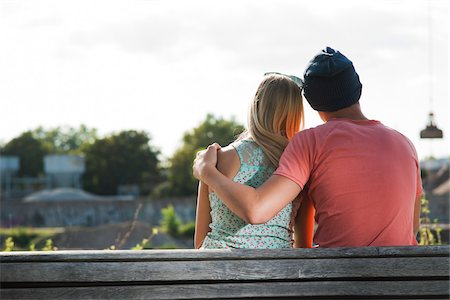 Backview of teenage boy with arm around teenage girl, sitting on bench outdoors, Germany Stock Photo - Premium Royalty-Free, Code: 600-06961034