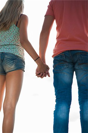 Backview of teenage boy and teenage girl holding hands, standing outdoors, Germany Stock Photo - Premium Royalty-Free, Code: 600-06961036