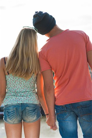 Backview of teenage boy and teenage girl holding hands, standing outdoors, Germany Stock Photo - Premium Royalty-Free, Code: 600-06961038