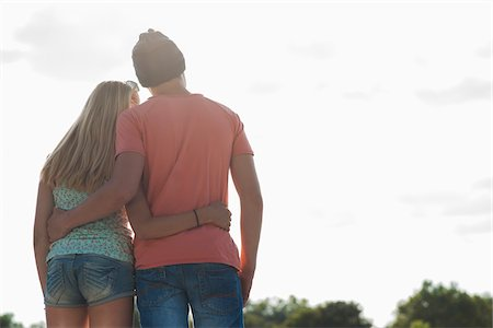 Backview of teenage boy and teenage girl with arms around each other, standing outdoors, Germany Stock Photo - Premium Royalty-Free, Code: 600-06961039