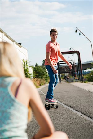 sitting - Backview of teenage girl in foreground and teenage boy on skateboard in background, Germany Stock Photo - Premium Royalty-Free, Code: 600-06961030
