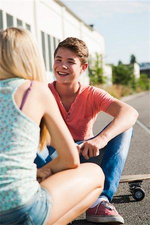 Teenage girl and teenage boy sitting on street, talking, Germany Stock Photo - Premium Royalty-Free, Code: 600-06961031