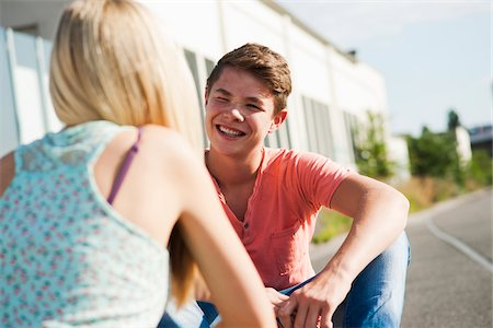 Teenage girl and teenage boy sitting on street, talking, Germany Stock Photo - Premium Royalty-Free, Code: 600-06961032