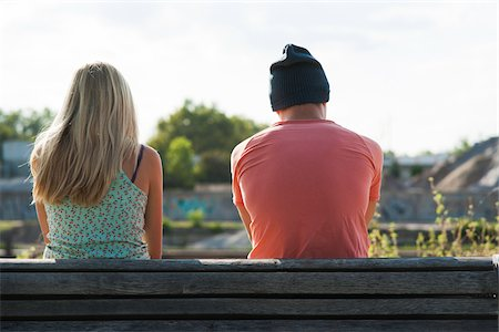 Backview of teenage girl and teenage boy sitting on bench outdoors, Germany Stock Photo - Premium Royalty-Free, Code: 600-06961033
