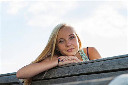 Portrait of teenage girl sitting on bench outdoors, looking at camera, Germany Stock Photo - Premium Royalty-Free, Code: 600-06961045