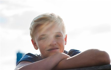Close-up portrait of boy outdoors, smiling at camera, Germany Stock Photo - Premium Royalty-Free, Code: 600-06961047
