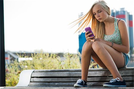 Teenage girl sitting on bench outdoors, looking at cell phone, Germany Stock Photo - Premium Royalty-Free, Code: 600-06961041