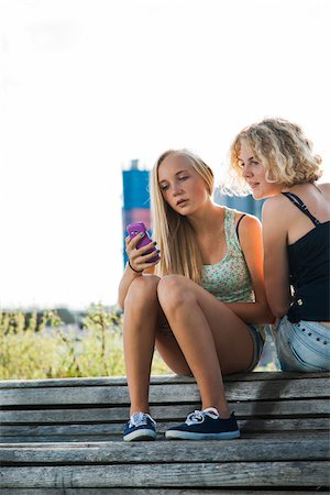 Teenage girls sitting on bench outdoors, looking at cell phone, Germany Stock Photo - Premium Royalty-Free, Code: 600-06961043