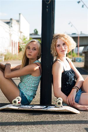 Portrait of teenage girls outdoors with skateboard, looking at camera, sitting on street, Germany Stock Photo - Premium Royalty-Free, Code: 600-06961051