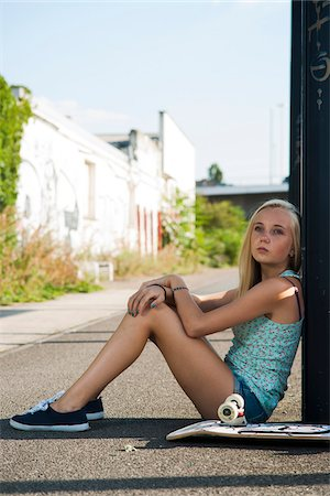 Portrait of teenage girl outdoors with skateboard, looking into the distance, sitting on street, Germany Stock Photo - Premium Royalty-Free, Code: 600-06961053