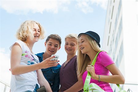 Group of teenagers standing outdoors looking at cell phone and talking, Germany Stock Photo - Premium Royalty-Free, Code: 600-06961061