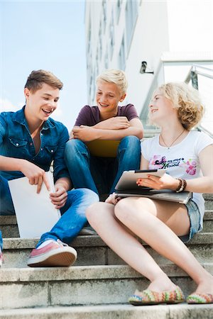 Teenagers sitting on stairs outdoors, talking and looking at tablet computer, Germany Stock Photo - Premium Royalty-Free, Code: 600-06961062
