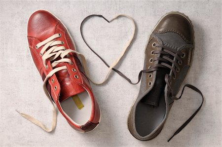 A man's shoe and a woman's shoe with laces tied together in a heart shape Stock Photo - Premium Royalty-Free, Code: 600-06961803