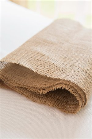 Folded burlap table runner on white tablecloth Stock Photo - Premium Royalty-Free, Code: 600-06961852