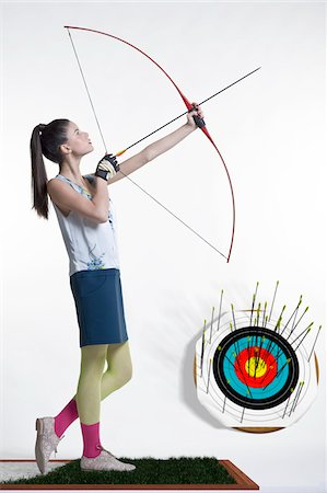 Side view of young, woman archer, aiming bow and arrow, studio shot on white background Stock Photo - Premium Royalty-Free, Code: 600-07066926
