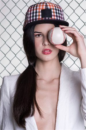 Close-up portrait of young woman wearing baseball cap and holding baseball in front of eye, studio shot on white background Stock Photo - Premium Royalty-Free, Code: 600-07066931